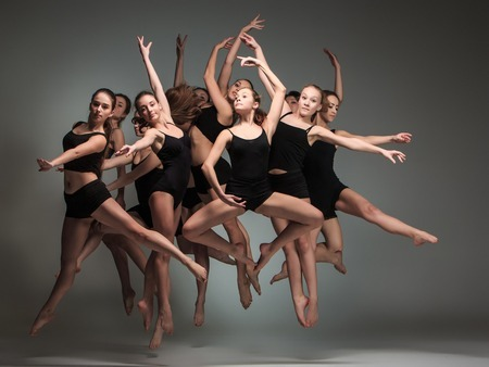 52275936 - the group of modern ballet dancers jumping on gray background