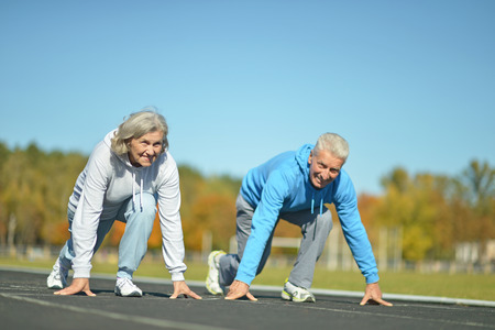 38983336 - happy fit senior couple jogging at stadium
