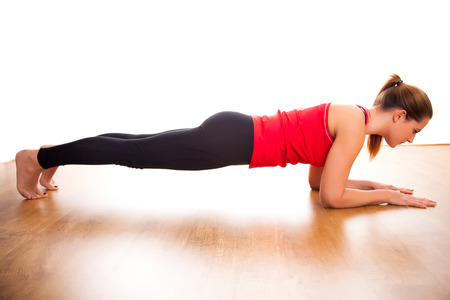 38859162 - young woman exercising - doing a plank in a studio