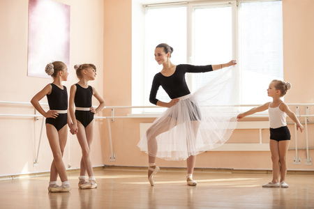 48996591 - young girl warming up and talking to younger classmates at ballet dancing class
