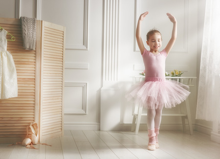 55145530 - cute little girl dreams of becoming a ballerina. child girl in a pink tutu dancing in a room. baby girl is studying ballet.