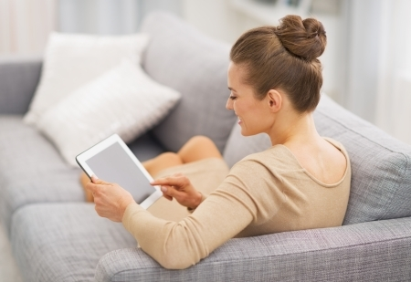 22665657 - young housewife sitting on couch using tablet pc . rear view